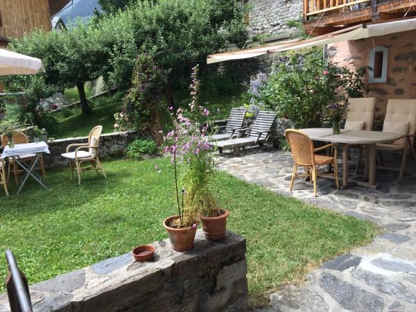 Tuin met tafel en stoelen onder luifel